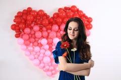 Donna castana sexy con i palloni ed i fiori rossi del cuore Fotografia Stock