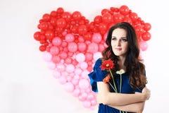 Donna castana sexy con i palloni ed i fiori rossi del cuore Fotografie Stock