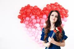 Donna castana sexy con i palloni ed i fiori rossi del cuore Fotografia Stock Libera da Diritti