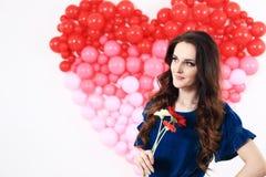 Donna castana sexy con i palloni ed i fiori rossi del cuore Immagini Stock Libere da Diritti