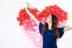 Donna castana sexy con i palloni ed i fiori rossi del cuore Immagini Stock