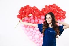 Donna castana sexy con i palloni ed i fiori rossi del cuore Immagine Stock