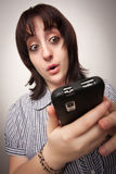 Donna castana sgomento che per mezzo del telefono cellulare Fotografia Stock Libera da Diritti