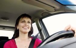 Donna castana sorridente che conduce automobile Immagine Stock