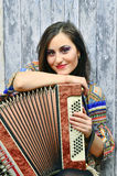 Donna castana sorridente che gioca la fisarmonica Immagini Stock