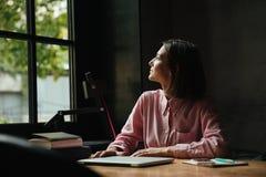 Donna castana sorridente che si siede dalla tavola in caffè Immagine Stock
