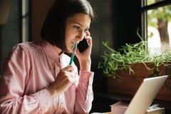 Donna castana sorridente che si siede dalla tavola in caffè Fotografia Stock