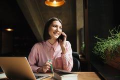 Donna castana sorridente che si siede dalla tavola con il computer portatile Fotografie Stock Libere da Diritti