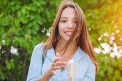 Donna castana sorridente dei giovani felici che mangia il gelato sugli alberi verdi fotografia stock libera da diritti