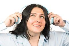 Donna castana sorridente felice con le cuffie che ascolta la musica isolata su fondo bianco Litening al concetto di musica immagini stock