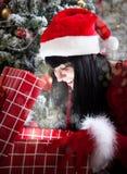 Donna castana stupita che apre un presente in pieno del Natale magico Immagini Stock