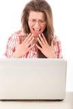 Donna casuale abbastanza colpita che esamina computer portatile Fotografie Stock