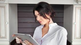 Donna casuale attraente che sorride facendo uso del PC della compressa al fondo d'annata della cucina archivi video