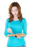 Donna casuale attraente con il libro che indica sul testo. Immagine Stock Libera da Diritti