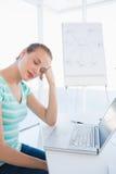 Donna casuale che dorme davanti al computer portatile all'ufficio Fotografia Stock