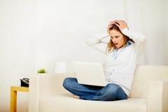 Donna casuale che lavora al sofà con un computer portatile Fotografie Stock