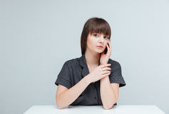 donna casuale che si siede alla tavola Immagini Stock