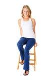 Donna casuale che si siede su una piccola scaletta fotografia stock libera da diritti