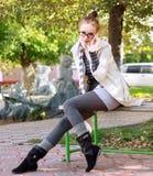 Donna casuale che si siede sul banco in sosta Fotografia Stock