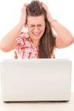 Donna casuale colpita che esamina computer portatile perché errore Fotografia Stock