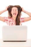 Donna casuale colpita con i vetri che esaminano computer portatile e che colgono Fotografia Stock
