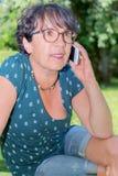 Donna casuale moderna che si siede al giardino, rivolgente allo smartphone Immagine Stock Libera da Diritti