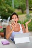 Donna casuale sorpresa con il computer portatile e lo smartphone fuori Fotografia Stock