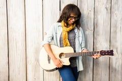 Donna casuale sorridente che gioca chitarra Immagine Stock