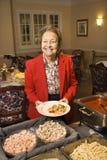Donna caucasica anziana nella riga del buffet. fotografia stock libera da diritti