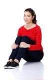 Donna caucasica attraente che si siede sul pavimento Fotografia Stock Libera da Diritti