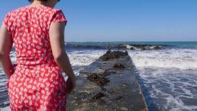 Donna caucasica attraente giovane che cammina sul pilastro che porta vestito rosso Gambe scalze che camminano verso il mare sul p stock footage