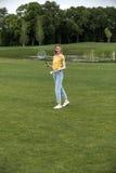 Donna caucasica che gioca volano sul campo verde in parco Immagine Stock Libera da Diritti