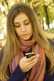 Donna caucasica che invita il suo telefono Immagine Stock Libera da Diritti