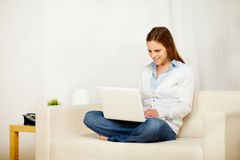 Donna caucasica che lavora al sofà con un computer portatile Fotografia Stock