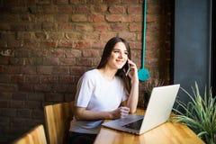 Donna caucasica che per mezzo del computer portatile e del telefono cellulare di un caffè Immagini Stock