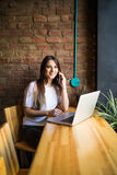 Donna caucasica che per mezzo del computer portatile e del telefono cellulare di un caffè Immagini Stock Libere da Diritti