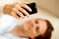 Donna caucasica che per mezzo di un telefono delle cellule nel paese Fotografia Stock