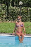 Donna caucasica che si siede sull'orlo del nuoto dello stagno all'aperto Fotografie Stock