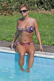 Donna caucasica che si siede sull'orlo del nuoto dello stagno all'aperto Immagini Stock Libere da Diritti