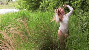 Donna caucasica che sta in body bianco sul flash della macchina fotografica della sponda del fiume archivi video
