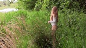 Donna caucasica che sta in body bianco sulla sponda del fiume stock footage