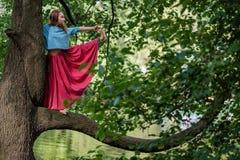Donna caucasica che sta nella posa di Utthita Hasta Padangusthasana dell'equilibrio di yoga Tiene il trank dell'albero Fotografia Stock