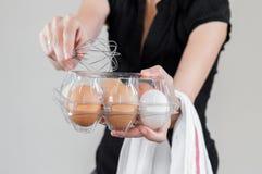 Donna caucasica con la camicia nera che tiene un frullino per le uova e una scatola delle uova di plastica in pieno delle uova de fotografia stock