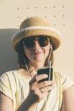 Donna caucasica dei bei giovani pantaloni a vita bassa con lo smartphone e il earp Immagine Stock Libera da Diritti