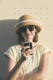 Donna caucasica dei bei giovani pantaloni a vita bassa con lo smartphone e il earp Fotografie Stock