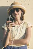 Donna caucasica dei bei giovani pantaloni a vita bassa con lo smartphone e il earp Fotografia Stock