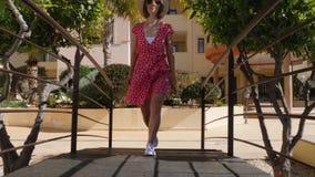 Donna caucasica felice giovane che cammina sul ponte nel giardino dell'hotel verso la macchina fotografica che indossa vestito, c video d archivio