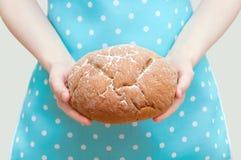 Donna caucasica in grembiule che tiene la pagnotta del pane di segale in sue mani immagine stock