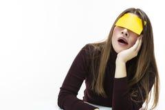 Donna caucasica pigra di sbadiglio in dolcevita di Borgogna con la nota appiccicosa gialla sulla sua fronte Contro priorità bassa fotografia stock libera da diritti