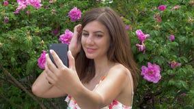 Donna caucasica Selfie di giovane bellezza con i fiori e sorridere archivi video